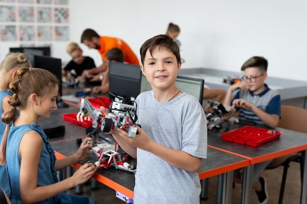 Portrait of male student building robot véhicule en classe de codage informatique après l'école