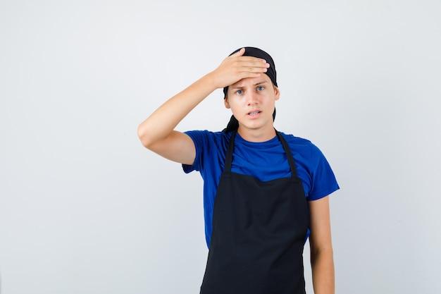 Portrait of male teen cook gardant la main sur le front en t-shirt, tablier et à la vue de face stressée