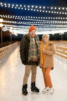 Portrait of mature couple smiling at camera pendant leur balade sur patins dans le parc