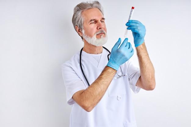 Portrait of mature doctor man avec tube d'échantillonnage du virus corona de la personne infectée en laboratoire