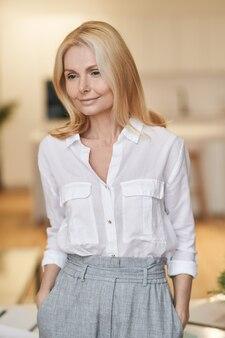 Portrait of mature woman wearing business tenue à côté tout en posant à la maison