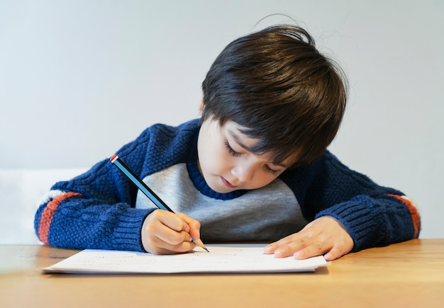 Portrait of school kid boy siting on table doing homework, happy child holding crayon writing, a boy drawing on white paper at the table, elementary school and homeschooling concept
