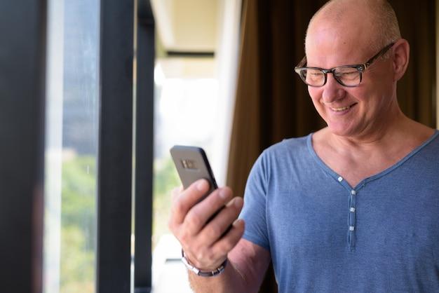 Portrait of senior bel homme scandinave se détendre à l'intérieur de la chambre de l'hôtel