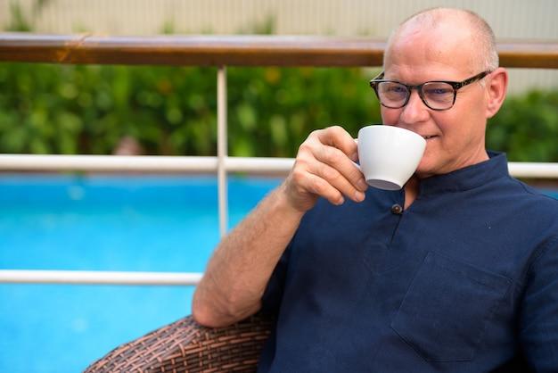 Portrait of senior bel homme de tourisme scandinave se détendre avec la nature sur la terrasse en plein air