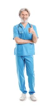 Portrait of senior male doctor montrant le geste du pouce vers le haut sur fond blanc