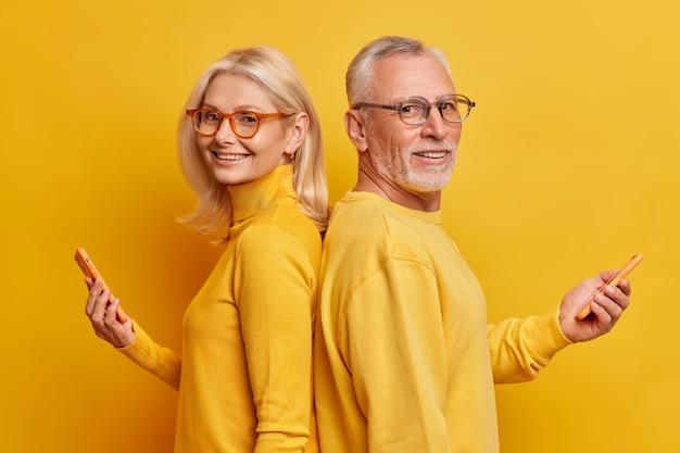 Portrait of senior woman and man stand de profil avec des gadgets modernes tenir smartphone ont la dépendance à la technologie porter des vêtements décontractés isolés sur mur jaune