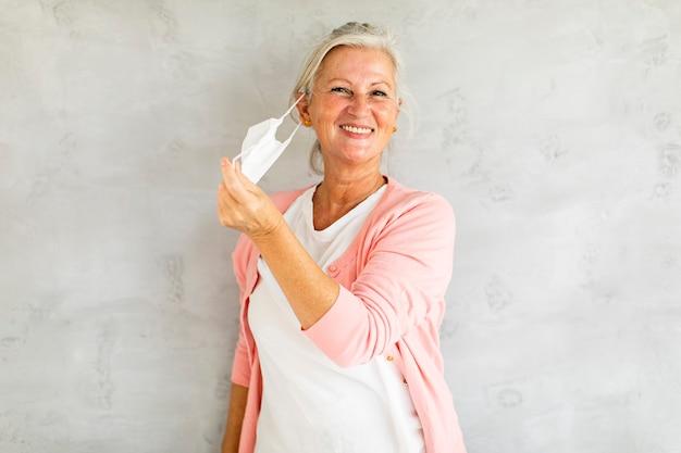 Portrait of senior woman décoller masque facial médical de protection pour la protection contre le virus