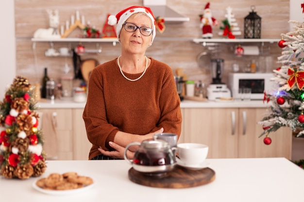 Portrait of senior woman with santa hat standing at table dans la cuisine décorée de noël