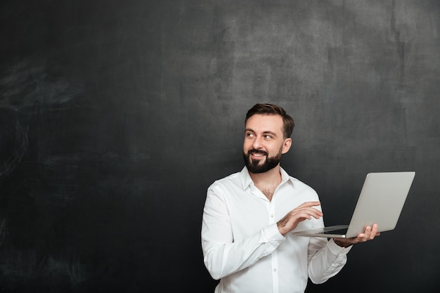 Portrait of smiling adult guy holding silver laptop et regardant de côté, isolé sur mur gris foncé
