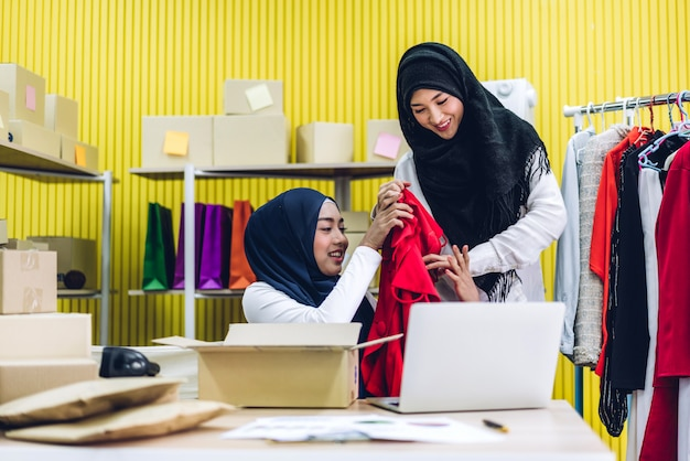 Portrait of smiling beaux propriétaires musulmans travaillant sur un ordinateur portable avec des boîtes à colis sur table à la maison