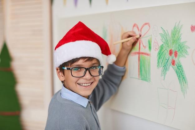 Portrait of smiling boy wearing santa hat et dessin sur les murs tout en profitant de cours d'art à noël, copiez l'espace
