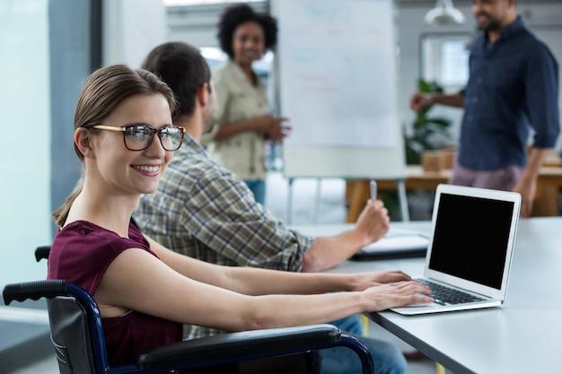 Portrait of smiling business executive en fauteuil roulant travaillant sur ordinateur portable en réunion