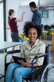 Portrait of smiling business executive handicapé en fauteuil roulant à l'aide de tablette numérique
