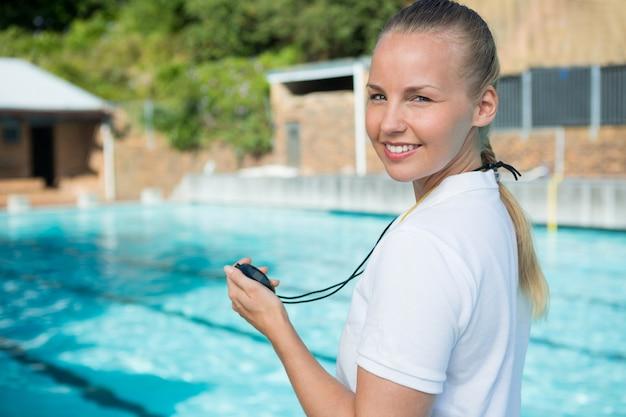 Portrait of smiling coach de natation tenant un chronomètre au bord de la piscine