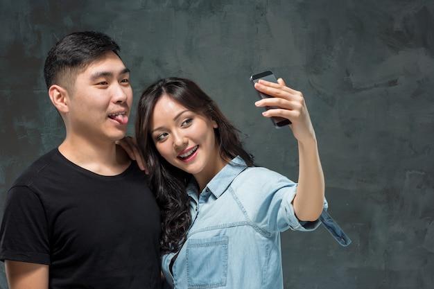 Portrait of smiling couple coréen sur un gris