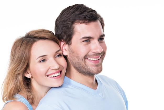 Portrait of smiling couple embrassant en casual à la recherche sur le côté - isolé