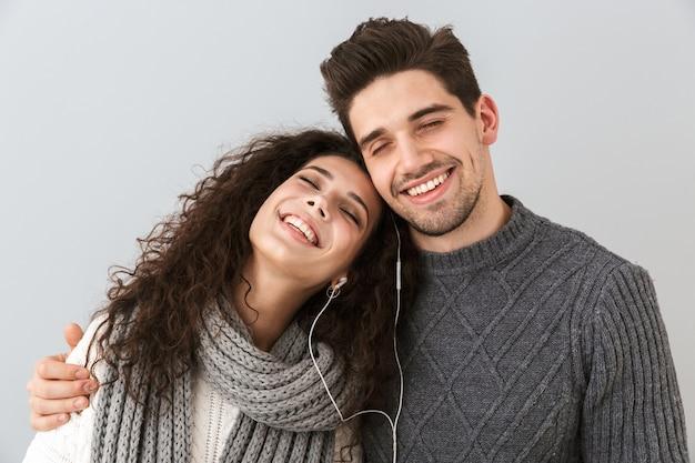 Portrait of smiling couple homme et femme écoutant de la musique avec des écouteurs, isolé sur mur gris