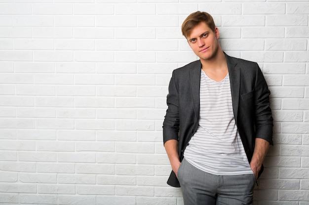 Portrait of smiling élégant homme d'affaires debout contre le mur de briques dans un bureau moderne
