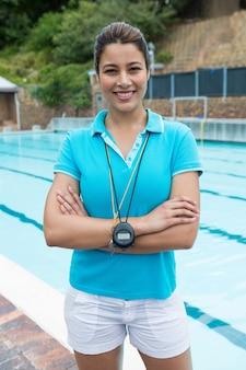 Portrait of smiling female coach debout avec les bras croisés près de la piscine