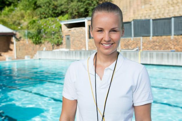 Portrait of smiling female coach debout près de la piscine au centre de loisirs
