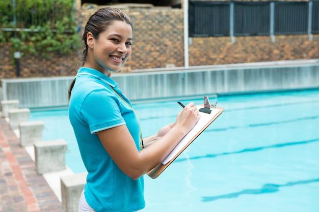 Portrait of smiling female coach écrit sur le presse-papiers près de la piscine