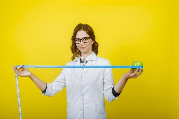 Portrait of smiling female doctor nutritionniste en robe blanche avec stéthoscope tenant un ruban à mesurer et apple isolé