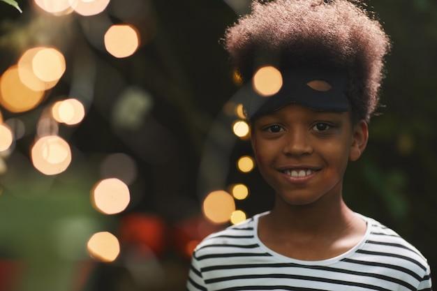 Portrait of smiling garçon afro-américain lors de la fête d'halloween en plein air avec des lumières, copiez l'espace