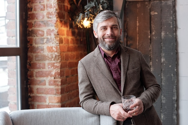Portrait of smiling handsome businessman avec barbe grise tenant un verre de whisky dans le hall loft