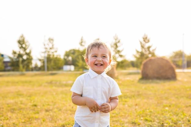 Portrait of smiling happy baby boy sur fond naturel en été