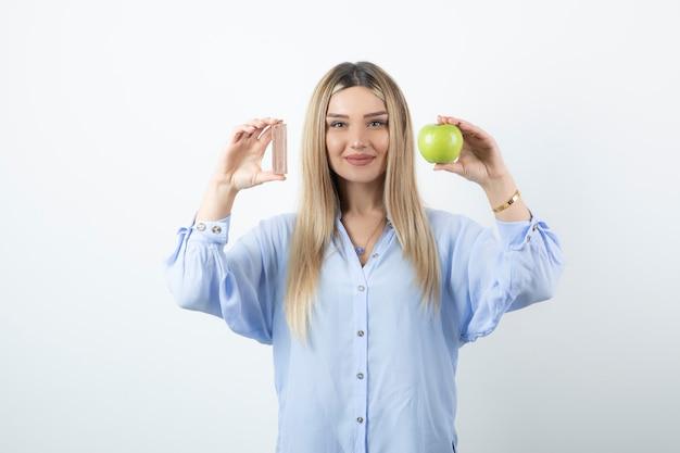 Portrait of a smiling happy girl holding pomme verte avec barre de chocolat contre le mur blanc