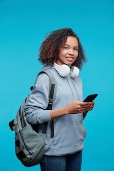Portrait of smiling hipster fille afro-américaine aux cheveux bouclés portant une sacoche sur le dos et un message texte sur smartphone