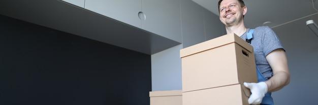 Portrait of smiling male gai transportant pile de boîtes. copiez l'espace sur le côté gauche. un travailleur heureux livre des cartons avec des objets personnels. concept de rénovation et de design d'intérieur