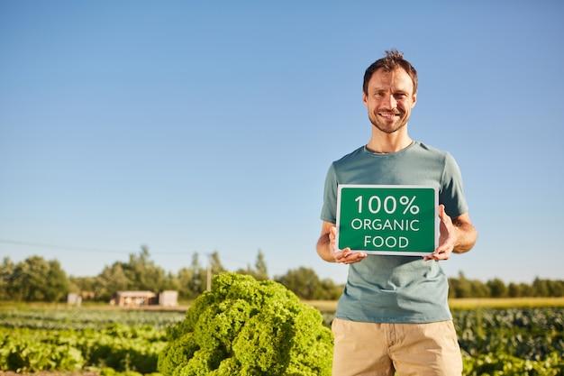 Portrait of smiling man holding bio signe de la nourriture et en se tenant debout à la plantation de légumes à l'extérieur au soleil, copiez l'espace