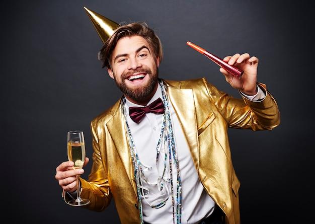 Portrait of smiling man holding flûte à champagne et souffleur de fête