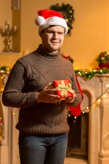 Portrait of smiling man in santa red hat holding red gift box at house