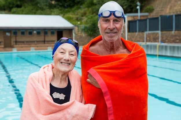 Portrait of smiling senior couple enveloppé dans une serviette au bord de la piscine