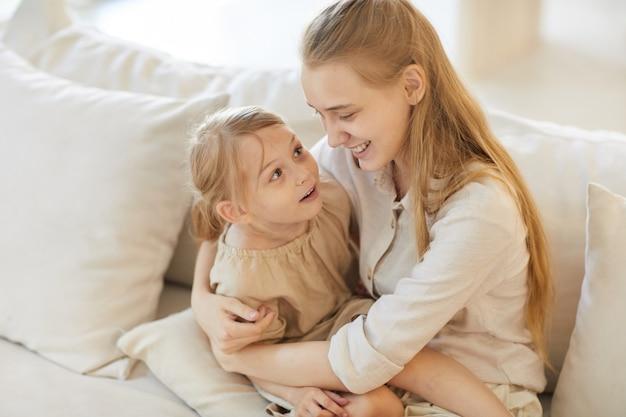 Portrait of smiling teenage girl holding cute little sister alors qu'il était assis sur un canapé blanc confortable à la maison
