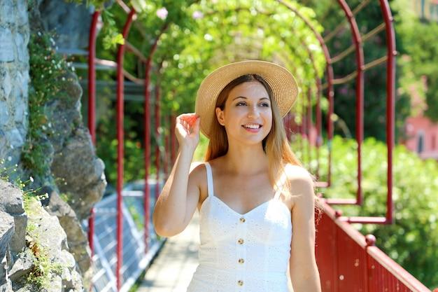 Portrait of smiling tourist woman exécute la promenade des amoureux à varenna sur le lac de côme, italie