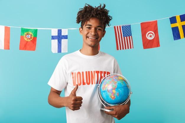 Portrait of a smiling young african man wearing t-shirt voluteer debout isolé sur mur bleu, montrant les pouces vers le haut