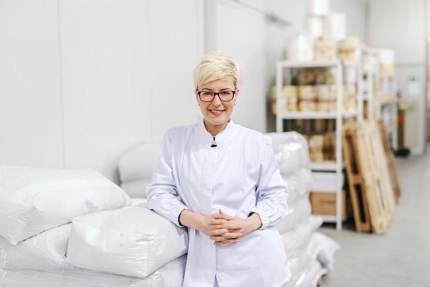 Portrait of smiling young blonde caucasian blonde woman in uniform stérile et lunettes s'appuyant sur des sacs de farine dans l'usine alimentaire.