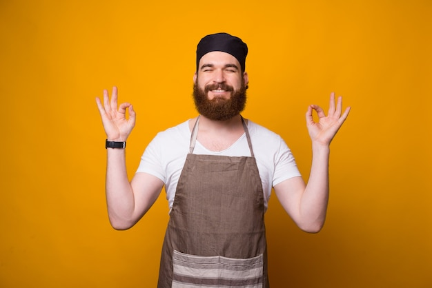 Portrait of smiling young chef man meditating over