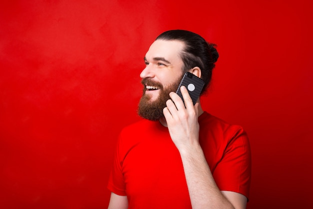 Portrait of smiling young man talking on smartphone sur mur rouge