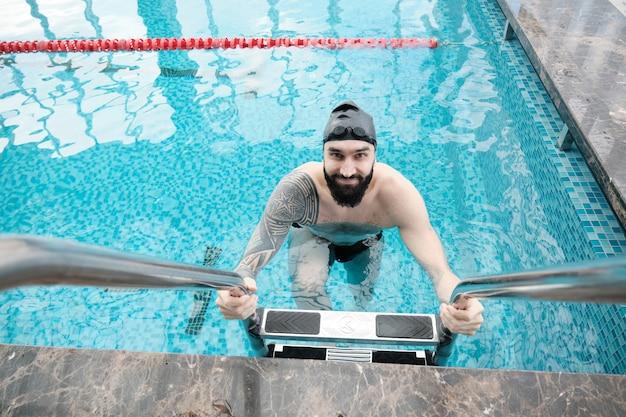 Portrait of smiling young nageur barbu en bonnet noir sortir de l'eau à l'aide d'escaliers dans la piscine