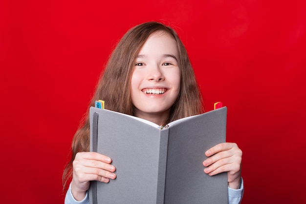 Portrait of smiling young school girl holding planificateur