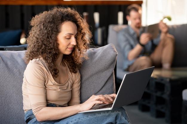 Portrait of smiling young smm manager aux cheveux bouclés assis sur un canapé confortable et travaillant avec un ordinateur portable au café