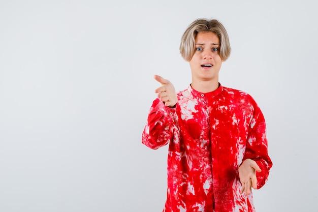 Portrait of teen blonde male faisant semblant de tenir quelque chose dans une chemise surdimensionnée et à la vue de face confuse