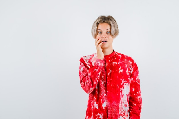 Portrait of teen blonde male avec la main sur la joue en chemise surdimensionnée et à la vue de face perplexe