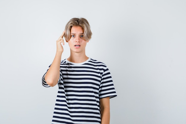 Portrait of teen boy gardant les doigts sur la tête en t-shirt et à la vue de face perplexe