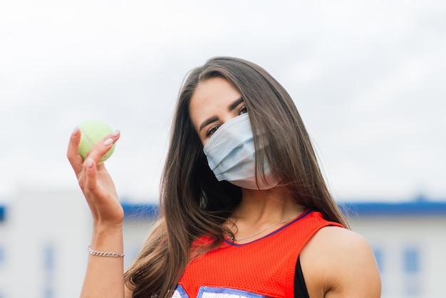 Portrait of tennis player girl holding raquette à l'extérieur avec des masques de protection