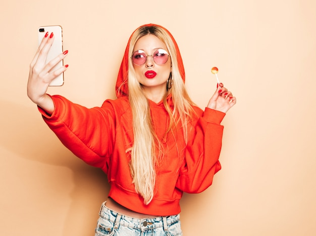 Portrait of young beautiful hipster bad girl in trendy jeans clothing and earring in her nose. sexy insouciant smiling blonde woman takes selfie.